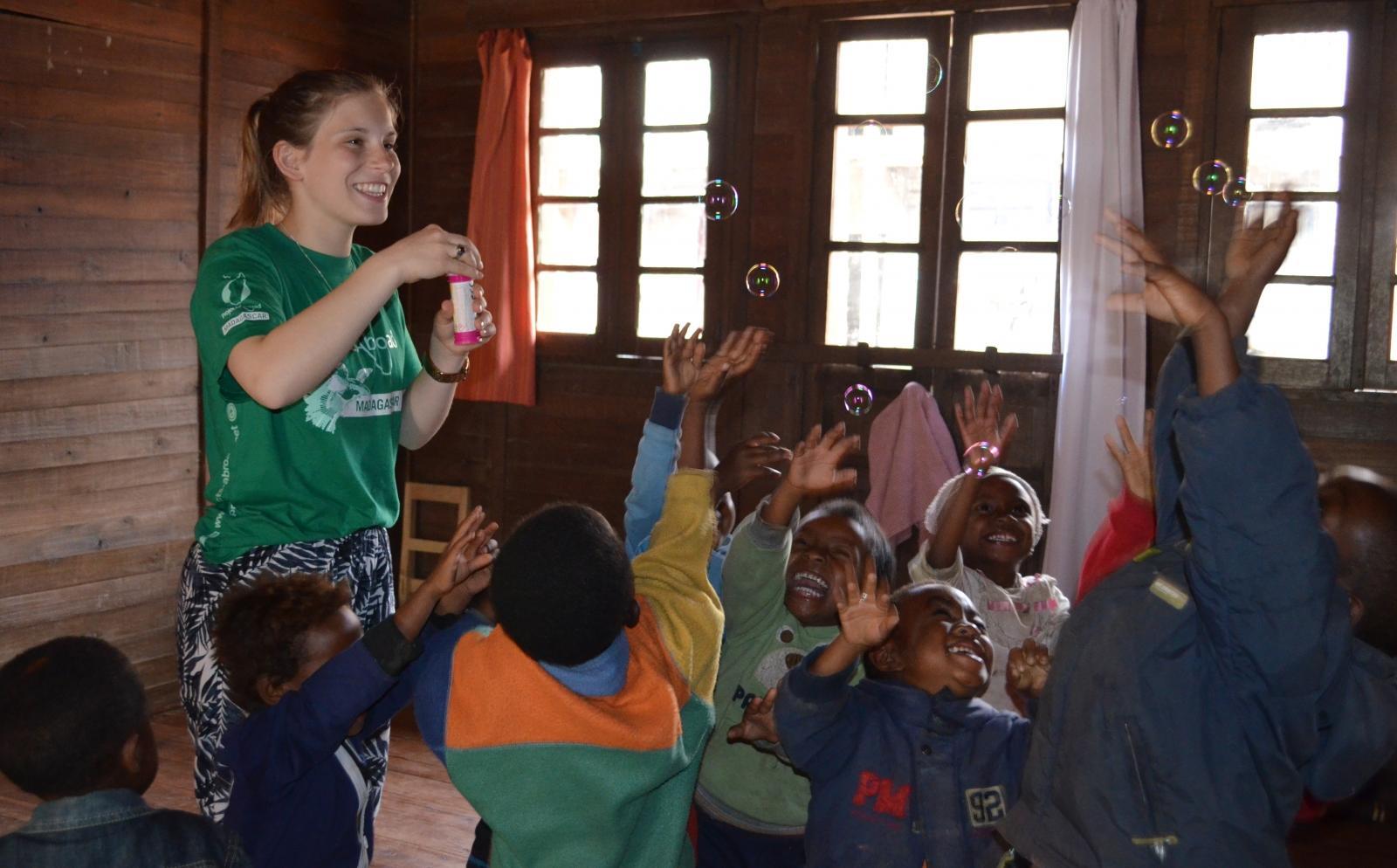 Una voluntaria social jugando con burbujas con niños de un jardín de infancia durante sus vacaciones solidarias en Madagascar.